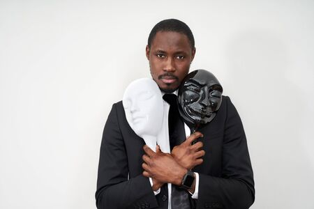 African young man wearing black suit holding white and black plastic masks revealing face Foto de archivo