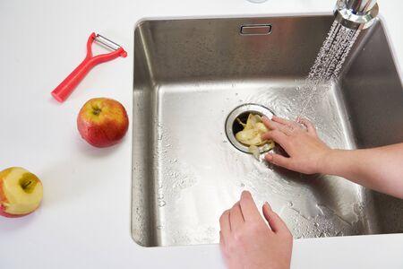 Food waste disposer machine in sink in modern kitchen