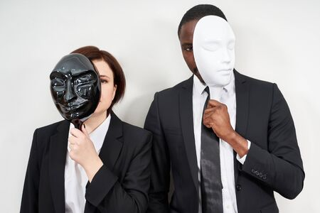African man and Caucasian woman wearing black suits hiding face with plastic masks Standard-Bild - 143298550