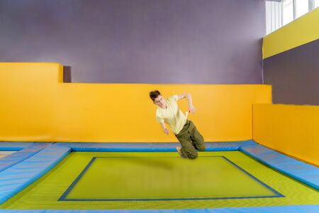 Happy smiling small kids jumping on indoors trampoline in entertainment center