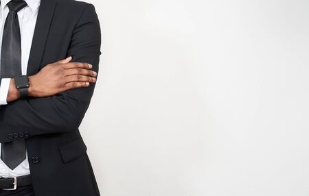 Cropped portrait of successful african man with arms crossed over grey background with copy space