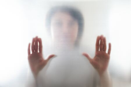 Diffused silhouette of female hands through frosted glass