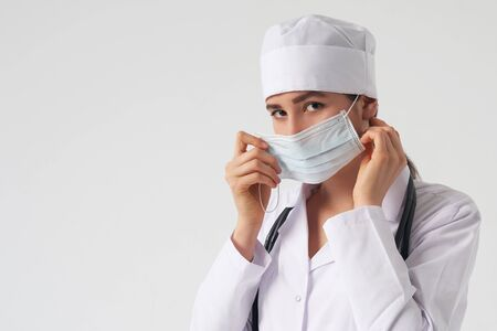 portrait of female doctor wearing protective mask and looking at camera posing against white background, copy space
