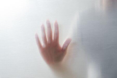 Diffused silhouette of female hands through plastic Imagens