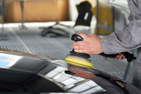 hands holding polisher to polish car in auto workshop