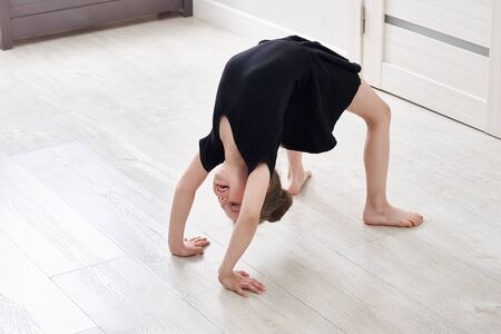 Little girl doing backbend gymnastics exercise at home