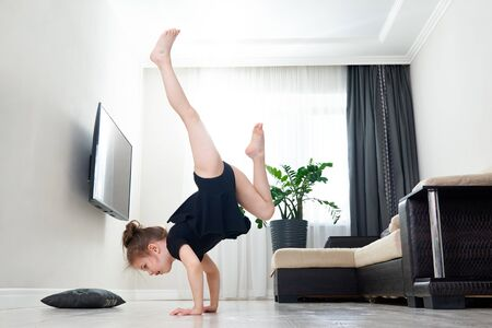 Little girl doing gymnastics at home standing on her hands upside down Фото со стока