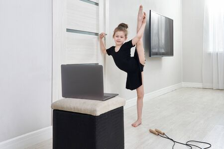 Little girl doing gymnastics exercises at home using online learning with laptop computer, internet education concept