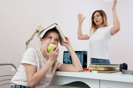 Mother and daughter fighting about homework, Upset mother is angry to little bored daughter, homeschooling, misunderstanding Stock Photo