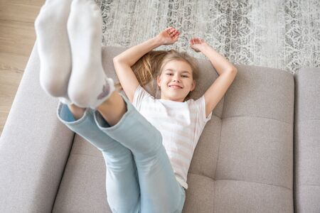 Preteen girl lying on couch with her feet raising up high