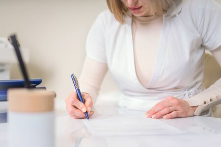 Female young doctor writing sitting at her office with medical equipment on a background. Healthcare and medical concept