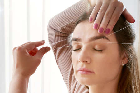 Cosmetologist plucks client eyebrows by thread in the beauty salon