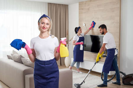 Professional cleaning service team cleans living room in modern apartment Reklamní fotografie