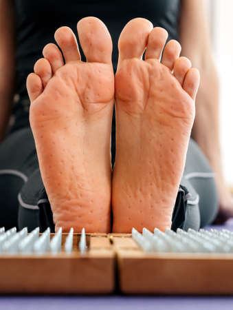 Feet and wooden board with sharp metal nails. Sadhu foot board. Yoga relaxation practice training