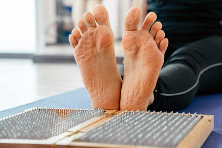 Feet and wooden board with sharp metal nails. Sadhu foot board. Yoga relaxation practice training Stock Photo