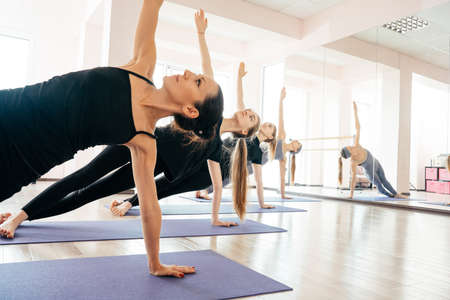 Group of attractive sport girls in sportswear working out in fitness hall. Young fit women doing yoga pose exercise on mats in gym