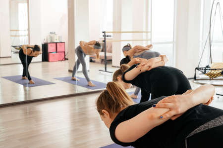 Group of attractive sport girls in sportswear working out in fitness hall. Young fit women doing yoga pose exercise on mats in gym 版權商用圖片