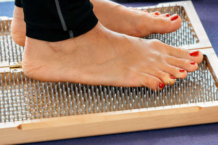 closeup of yoga person standing on sadhu board with sharp nails
