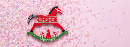 Christmas tree wooden toy of rocking horse on pink background with glitter. Flat lay, top view of with copy space