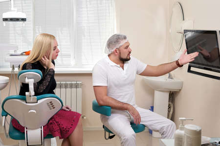 Dentist talking to patient, pointing at blank monitor