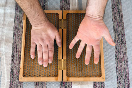 Man touching yoga wooden sadhu board with sharp nails