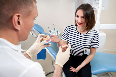 Male dentist showing his female patient a dental implant Zdjęcie Seryjne