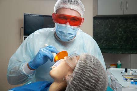 Dentist doing procedure with dental curing UV light in clinic 版權商用圖片