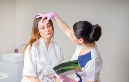 Young pretty woman came to a beauty salon and consults with a beautician on anti-aging treatments.