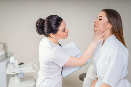 Professional cosmetician examining face skin of girl in clinic of esthetic cosmetology Imagens