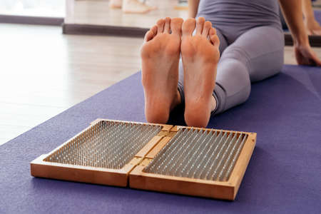 Feet and wooden board with sharp metal nails. Sadhu foot board. Yoga relaxation practice training Reklamní fotografie