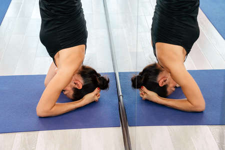 Young attractive yogi woman practicing yoga concept, doing headstand pose, working out, wearing sportswear
