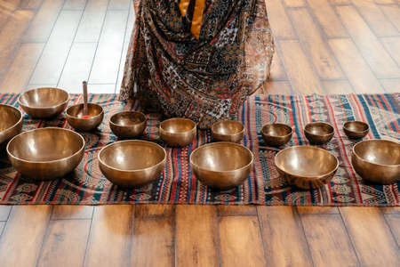 Tibetan handcrafted singing bowls on the floor in yoga class, sound therapy concept