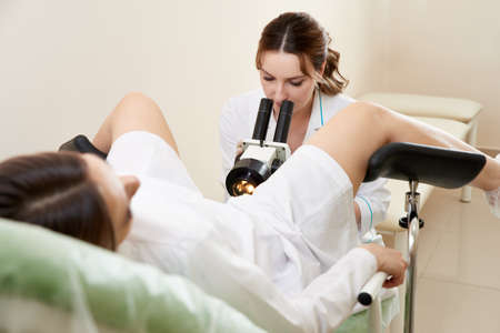 Gynecologist examining a patient with a microscope in modern medical clinic