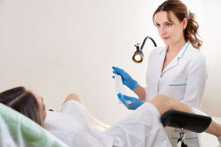 Gynecologist using vaginal swab for STD testing young patient