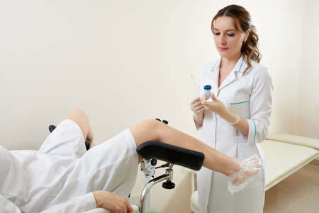 Gynaecologist examining a patient sitting on gynecological chair