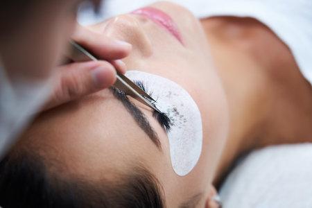 Eyelash extension procedure with tweezers in beauty salon