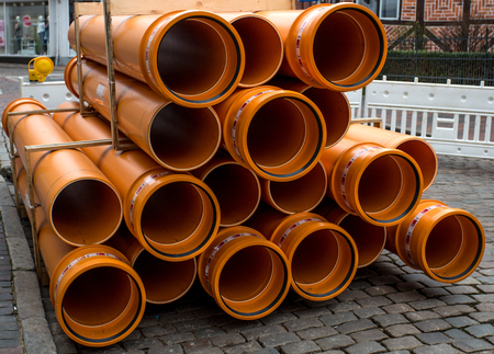 orange PVC pipes stacked in construction site Stock Photo