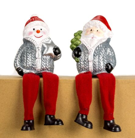 two Santa Clauses are sitting on a box