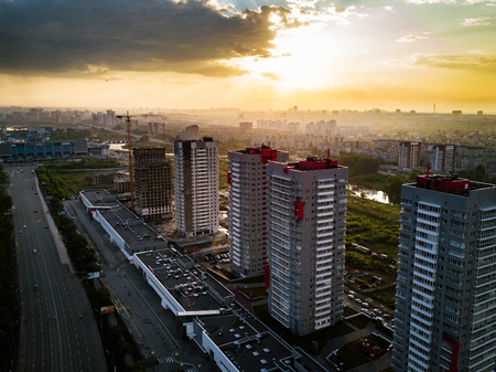 Aerial drone view of constructing of new residential area, silhouettes of construction crane on the background of the evening sun after the rain, Chelyabinsk, Russia Archivio Fotografico