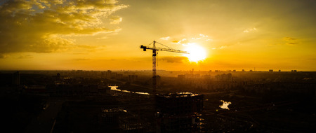 Silhouette of construction crane on the background of the warm evening sun, construction of a new district, Chelyabinsk, Russia