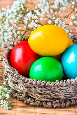 Colored painted eggs in a wattled basket with flowers  photo