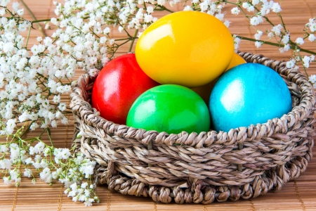 wattled: Colored painted eggs in a wattled basket with flowers