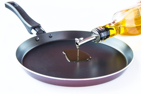 frying pan: Olive oil poured into the frying pan from the bottle