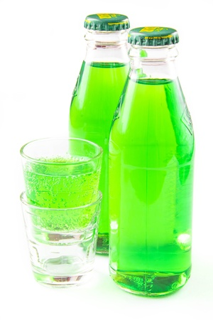 potation: Green lemonade in  two bottle and small glass on white Stock Photo