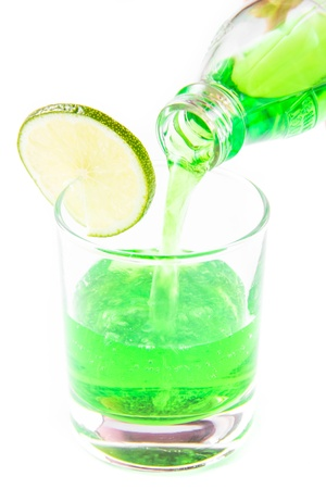 Tarragon green drink is poured from the bottle into a glass with lime on white