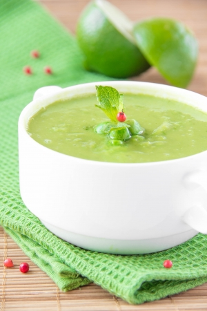 velvety: Velvety cream soup from a gentle green peas with mint and lime on green towel Stock Photo