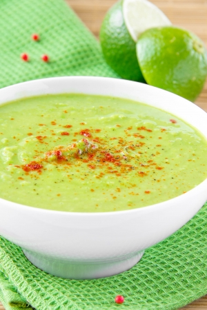 velvety: Velvety cream soup from a gentle green peas with mint and lime in white bowl on green towel