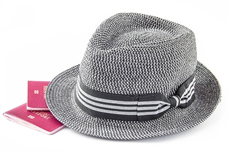 descriptor: Sun hat and red foreign passport on white