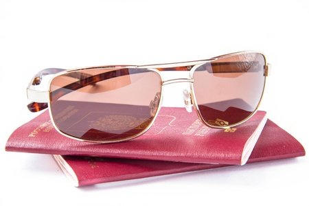 descriptor: Gold sun glasses on red passport for travelling abroad Stock Photo