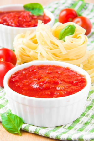 Italian tomato sauce in a white cup with raw pasta, basil and cherry tomatoes on purple towel photo